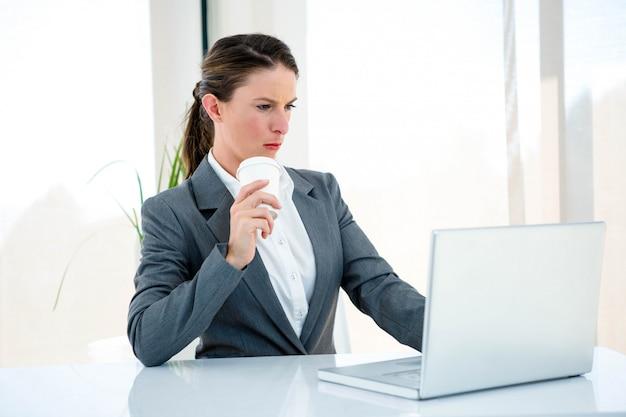 Ernsthafte geschäftsfrau, an ihrem schreibtisch, auf ihrem laptop tippen und kaffee trinken