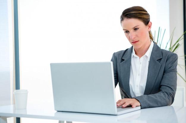 Ernsthafte geschäftsfrau, an ihrem schreibtisch, schreibend auf ihrem laptop