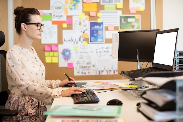 Ernsthafte geschäftsfrau, die am digitalisierer arbeitet, während tastatur verwendet wird