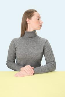 Ernsthafte geschäftsfrau, die am tisch auf einem blauen studio sitzt.
