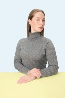 Ernsthafte geschäftsfrau, die am tisch auf einem rosa studiohintergrund sitzt. das porträt im minimalismusstil