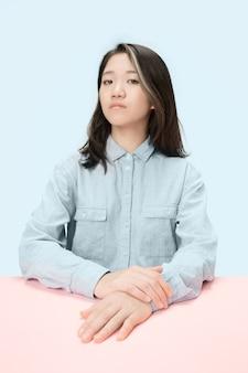 Ernsthafte geschäftsfrau, die am tisch sitzt und kamera lokalisiert auf trendigem blauem studiohintergrund betrachtet. schönes, junges gesicht.