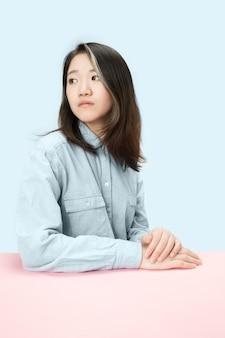 Ernsthafte geschäftsfrau, die am tisch sitzt und links lokalisiert auf trendigem blauem studiohintergrund betrachtet. schönes, junges gesicht. weibliches porträt in halber länge.