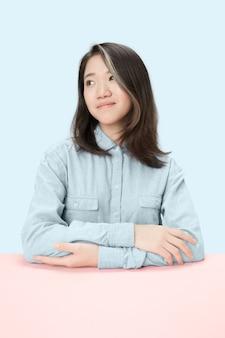 Ernsthafte geschäftsfrau, die am tisch sitzt und links lokalisiert auf trendigem blauem studiohintergrund betrachtet. schönes, junges gesicht.