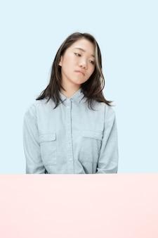 Ernsthafte geschäftsfrau, die am tisch sitzt und lokal auf den trendigen blauen studiohintergrund schaut. weibliches porträt in halber länge.