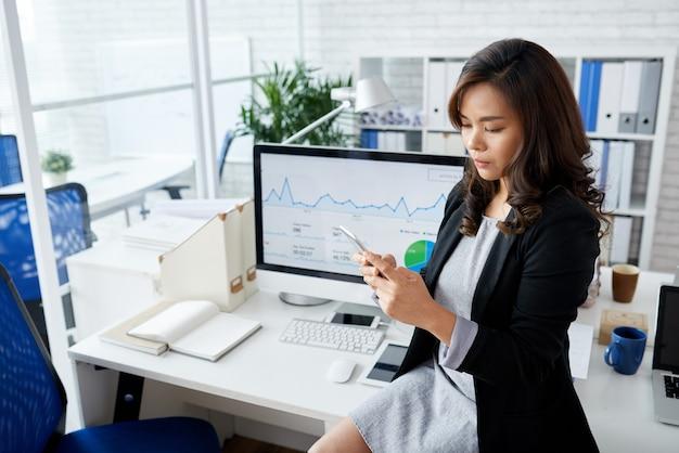 Ernsthafte geschäftsfrau, die auf dem schreibtisch sitzt und wichtige textnachrichten von kollegen liest, die...