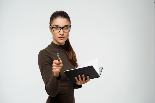 Ernsthafte geschäftsfrau, die auf sie zeigt, halten sie notizbuch