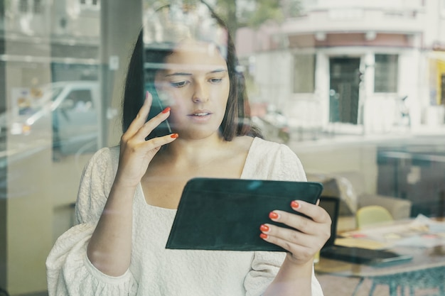 Ernsthafte geschäftsfrau, die auf zelle spricht, tablette benutzt und bildschirm betrachtet