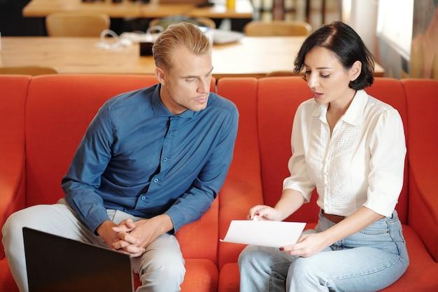 Ernsthafte geschäftsfrau, die dem kollegen bericht oder vertrag zeigt, wenn sie sich im café treffen?