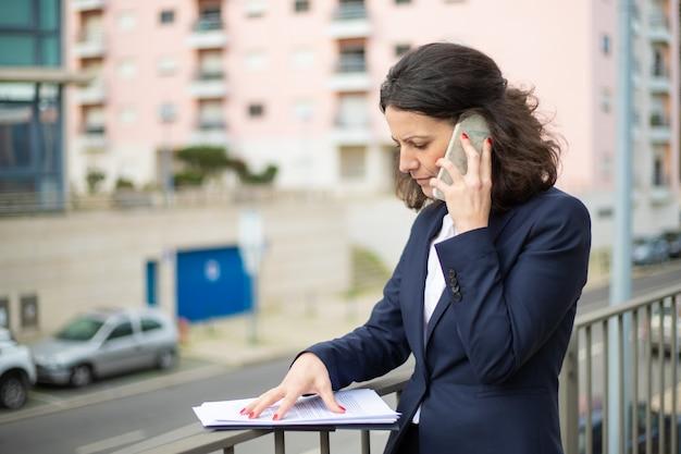 Ernsthafte geschäftsfrau, die durch smartphone spricht und papiere betrachtet