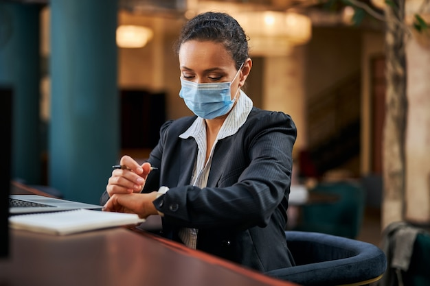 Ernsthafte geschäftsfrau, die im café ist und die zeit überprüft, während sie auf das treffen wartet?