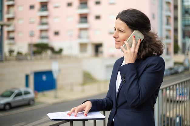 Ernsthafte geschäftsfrau, die per smartphone spricht