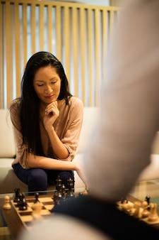 Ernsthafte geschäftsfrau, die schach mit männlichem kollegen spielt