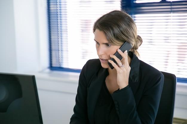 Ernsthafte geschäftsfrau in der jacke, die auf mobiltelefon spricht, während computer am arbeitsplatz im büro verwendet wird. mittlerer schuss. digitales kommunikations- und multitasking-konzept