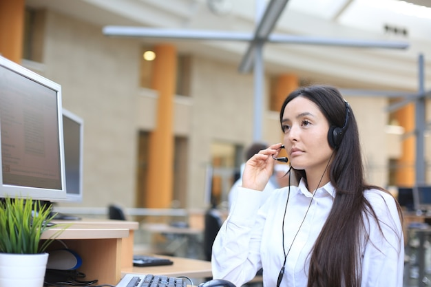 Ernsthafte geschäftsfrau mit kopfhörern, die webinar auf dem laptop ansieht, notizen macht, computerkurse lernt, anrufe tätigt, an online-konferenzen teilnimmt, dolmetscherübersetzungskurse