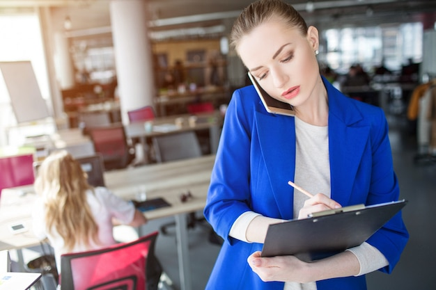 Ernsthafte geschäftsfrau schreibt informationen auf das tablett. sie spricht mit dem kunden.