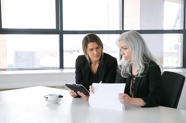 Ernsthafte geschäftsfrauen diskutieren berichte. zwei weibliche fachleute sitzen zusammen, halten dokumente, verwenden tablette und sprechen. kommunikationskonzept