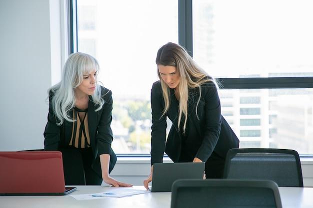 Ernsthafte geschäftsfrauen diskutieren projekt im besprechungsraum, stehen am tisch und schauen sich inhalte auf dem laptop an. vorderansicht. geschäftskommunikationskonzept