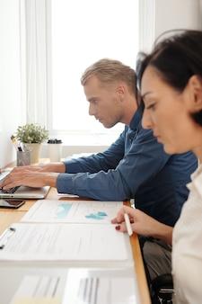 Ernsthafte geschäftsleute, die am schreibtisch an einem projekt arbeiten, auf dem laptop tippen und dokumente unterschreiben
