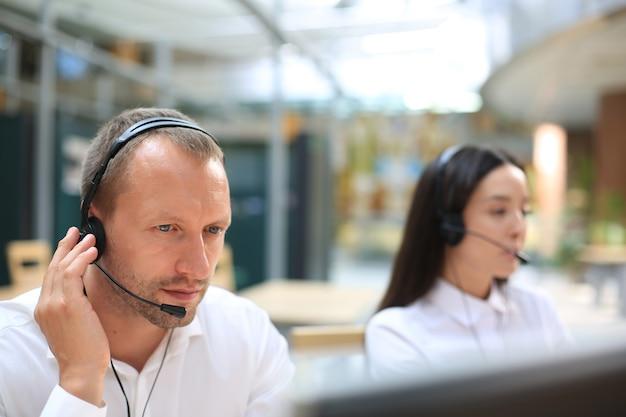 Ernsthafte geschäftsleute in kopfhörern, die webinar auf dem laptop ansehen, notizen machen, computerkurse lernen, anrufe tätigen, an online-konferenzen teilnehmen, dolmetscherübersetzungstrainingskurse