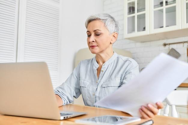 Ernsthafte grauhaarige reife geschäftsfrau, die am esstisch unter verwendung des laptops für fernarbeit sitzt und papiere hält. frau im ruhestand, die online-zahlungen über tragbare computer macht. alter, technik, beruf