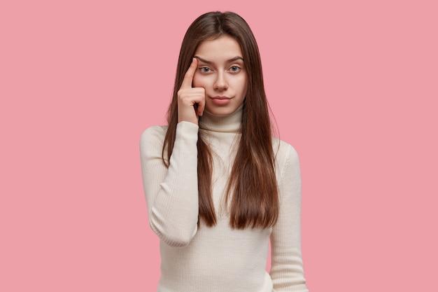 Ernsthafte, gut aussehende frau sieht selbstbewusst aus, hält den finger an den schläfen, zieht die augenbrauen hoch und hat langes dunkles haar