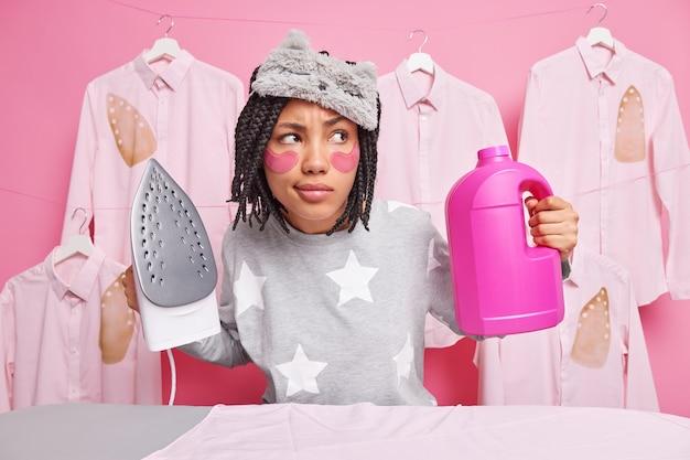 Ernsthafte hausfrau, die mit nachdenklichem ausdruck konzentriert ist, wäscht und bügelt zu hause bei hausarbeit, umgeben von gebügelter kleidung im innenbereich