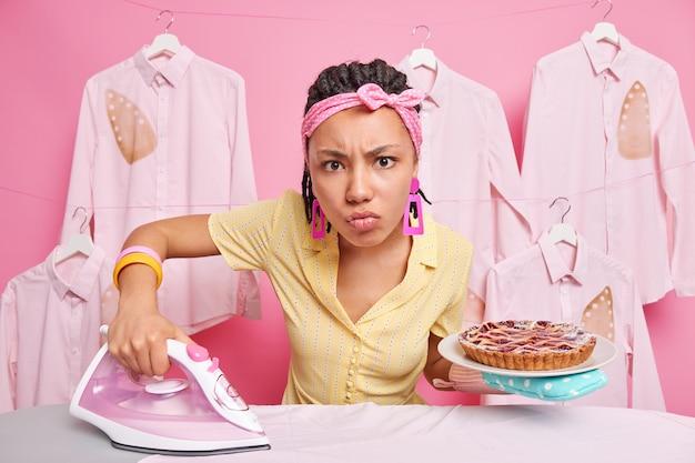 Ernsthafte hausfrau, die zu hause mit kochen und bügeln beschäftigt ist, hält köstlichen gebackenen kuchen und elektrisches bügeleisen in der nähe des bügelbretts in häuslicher kleidung, die damit beschäftigt ist, hausarbeiten zu erledigen, hat einen genervten ausdruck