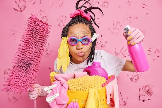 Ernsthafte hausfrau gibt vor, superheld zu sein, schaut aufmerksam in die kamera hält waschmittel schmutzigen mopp hat wäsche einen jährlichen großen reinigungstag macht das haus makellos trägt eine schutzbrille gummihandschuhe t-shirt