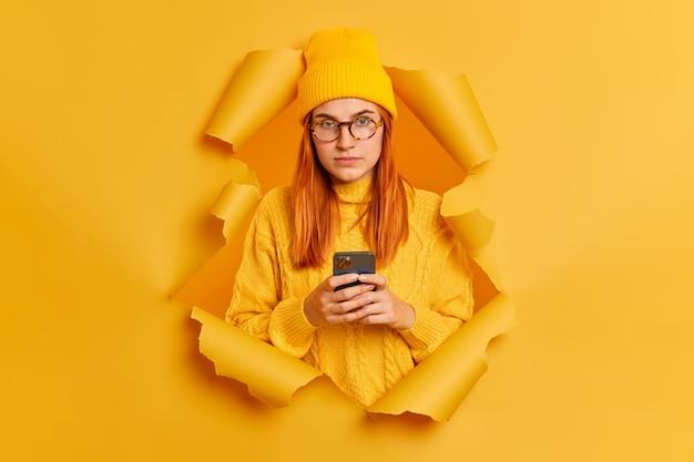 Ernsthafte hübsche rothaarige frau mit smartphone, trägt gelben hut und pullover, bricht durch papierwand