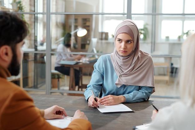Ernsthafte junge arabische frau im hijab, die vor personalmanagern am tisch sitzt und beim vorstellungsgespräch einen fragebogen ausfüllt