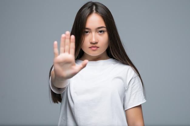 Ernsthafte junge asiatische frau, die stoppgeste mit ihrer handfläche zeigt, während lokalisiert über grauem hintergrund steht