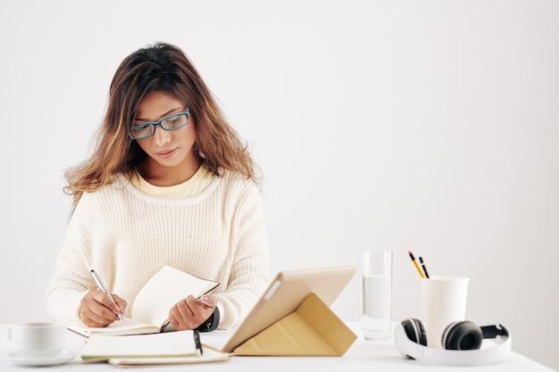 Ernsthafte junge asiatische geschäftsfrau mit brille, die am schreibtisch arbeitet und pfannen und kreative ideen aufschreibt
