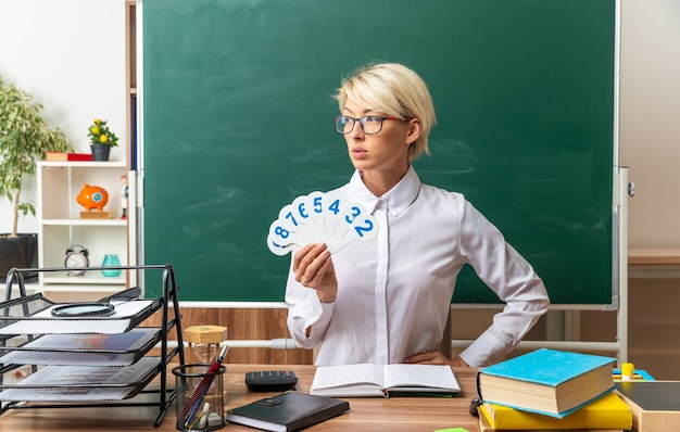 Ernsthafte junge blonde lehrerin mit brille, die am schreibtisch mit schulmaterial im klassenzimmer sitzt und nummernfächer hält, die die hand auf der taille halten und auf die seite schauen