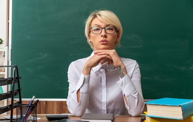 Ernsthafte junge blonde lehrerin mit brille, die am schreibtisch mit schulwerkzeugen im klassenzimmer sitzt und die hände unter dem kinn zusammenhält und in die kamera schaut