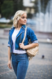 Ernsthafte junge blonde mädchenfrau auf straßenwegquadrat-fontain, gekleidet in blue jeans suite mit tasche auf ihrer schulter in sonnigem tag
