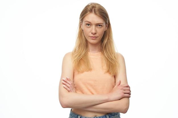 Ernsthafte junge dame mit blondem langem gesundem haar, trägt orangefarbenes oberteil und jeanshose, hält die hände auf der brust gekreuzt und zieht die augenbrauen hoch