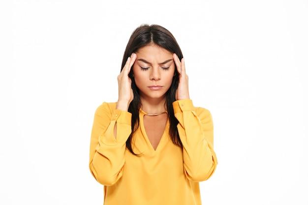Ernsthafte junge dame mit kopfschmerzen im gelben hemd