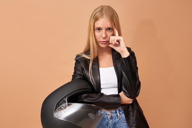 Ernsthafte junge fahrerin, die schutzhelm hält, der von der arbeit am motorrad nach hause pendelt