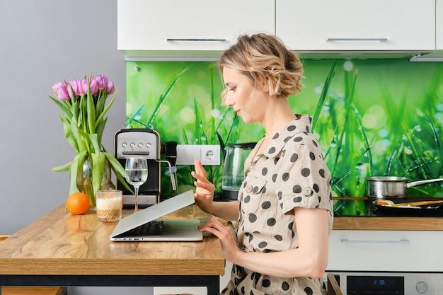 Ernsthafte junge frau beginnt arbeitstag im home office, sie öffnet die abdeckung ihres laptops