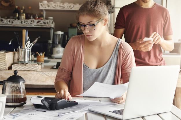 Ernsthafte junge frau, die rechteckige brille trägt, die ausgaben berechnet, während familienbudget mit generischem laptop und taschenrechner zu hause tut