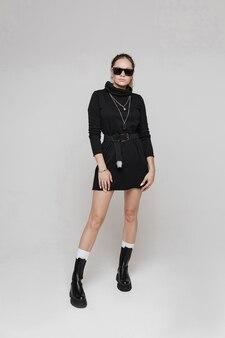 Ernsthafte junge frau, die sonnenbrille mit stiefeln und einem kleid trägt, das mit einem fuß vorwärts steht. modekonzept