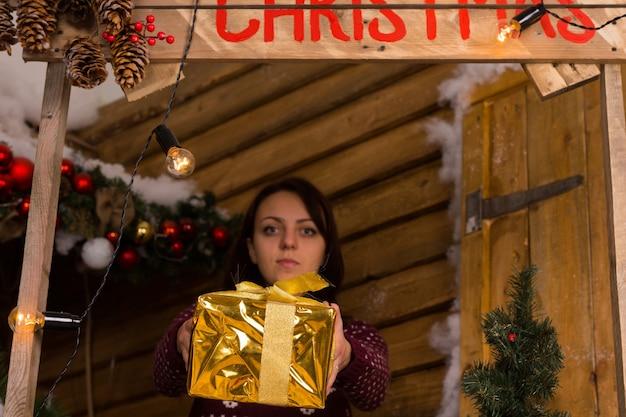 Ernsthafte junge frau im holzhaus, die eine goldene geschenkbox gibt, während sie in die kamera schaut.