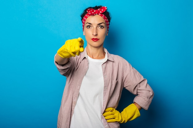 Ernsthafte junge frau im roten haarband, reinigungshandschuhe zeigt finger vor ihr gegen blaue oberfläche