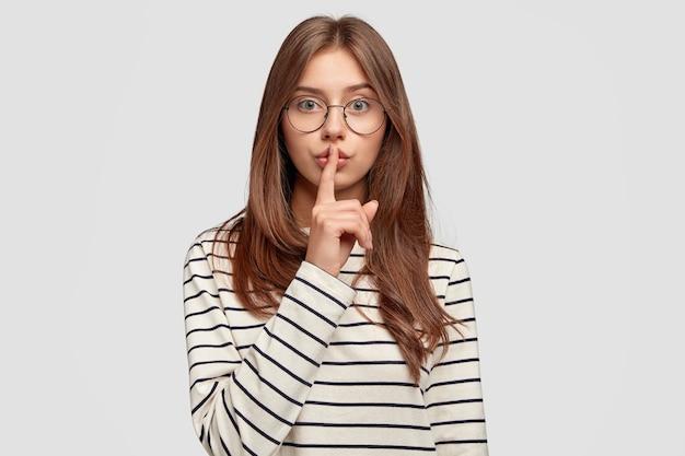 Ernsthafte junge frau mit brille, die gegen die weiße wand aufwirft
