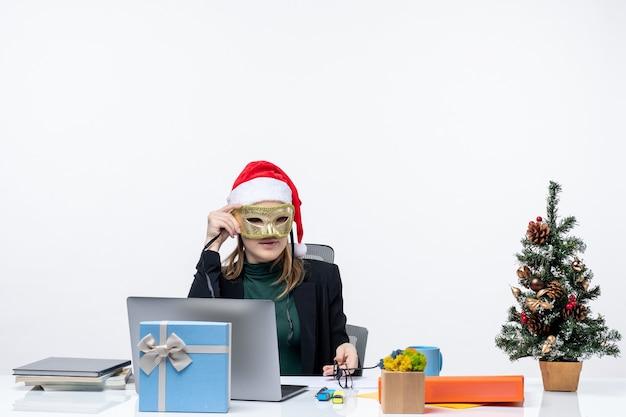 Ernsthafte junge frau mit weihnachtsmannhut, der brillen hält und an einem tisch mit einem weihnachtsbaum und einem geschenk darauf im büro auf weißem hintergrund sitzt