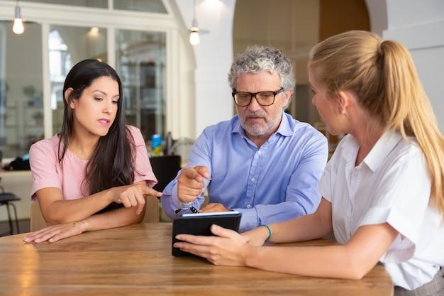 Ernsthafte junge frau und reifer mann treffen sich mit weiblichem fachmann, beobachten präsentation auf tablette und zeigen auf bildschirm