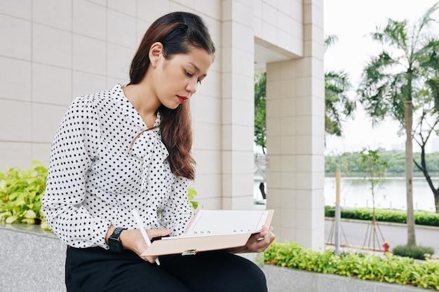 Ernsthafte junge gemischte geschäftsfrau, die draußen sitzt und notizen in ihrem planer macht