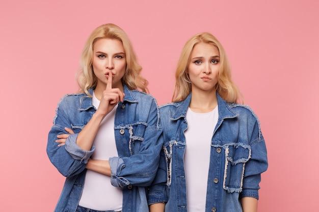 Ernsthafte junge hübsche blonde dame, die hand mit stiller geste zu ihrem mund hebt, während sie bittet, geheim zu halten, über rosa hintergrund mit verwirrter blonder frau stehend