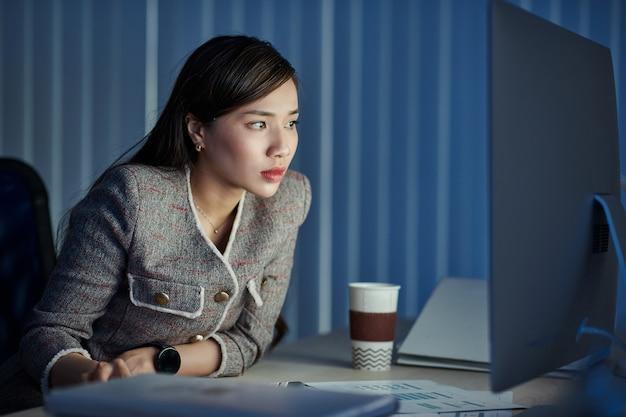 Ernsthafte junge hübsche geschäftsdame, die dokument auf leuchtendem bildschirm liest, wenn sie spät in der nacht im büro arbeitet
